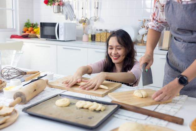 W domu kat uśmiechnięta, wspaniała kobieta i jej przyjaciółka wspólnie pieką chleb.