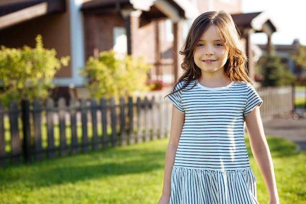 W domu. portret uroczej drobnej dziewczyny w pasiastej sukience stojącej w pobliżu domu i uśmiechającej się do kamery