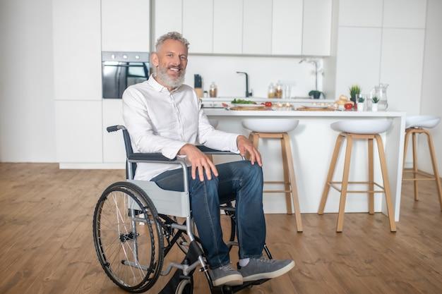W domu. siwowłosy dojrzały niepełnosprawny mężczyzna w kuchni