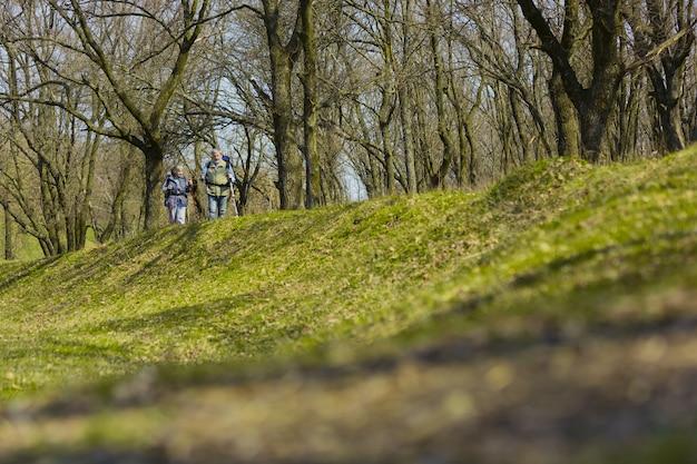W drodze razem. starsza rodzina para mężczyzna i kobieta w strój turystyczny spaceru na zielonym trawniku w pobliżu drzew w słoneczny dzień. pojęcie turystyki, zdrowego stylu życia, relaksu i wspólnoty.