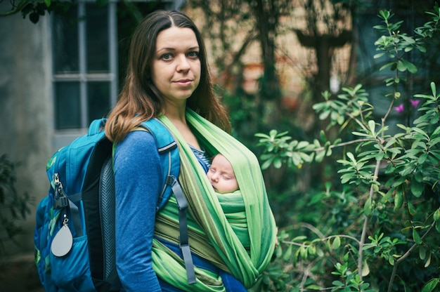 W dżungli chodzi młoda matka z dzieckiem na temblaku
