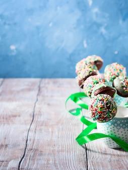 W filiżankach wyskakuje kolorowe ciasto czekoladowe. karta pionowa