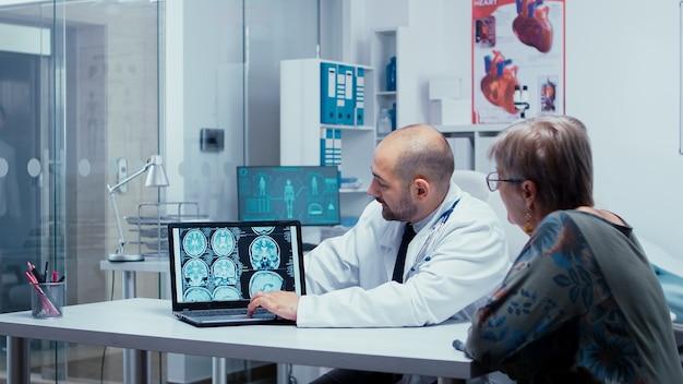 W gabinecie lekarskim rozmawiam o skanach mózgu, ct, mri i prześwietleniu rentgenowskim na ekranie laptopa dla starszej kobiety. diagnostyka mózgu, obraz medyczny ct, mri lub rtg w nowoczesnym szpitalu prywatnym lub