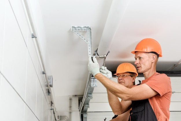 W garażu pracownicy montują windy.