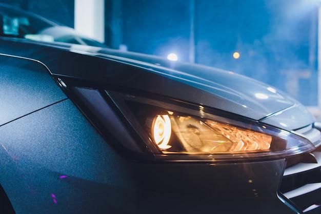 W garażu w salonie samochodowym środkowe reflektory samochodu są bardzo blisko, wyłączając się, sprawdzając wymiary przednich świateł