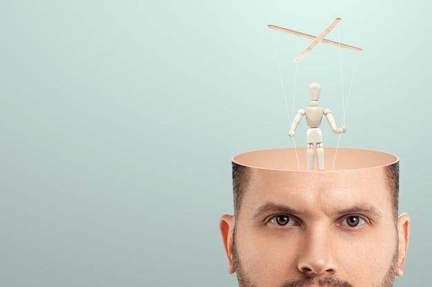 W Głowie Mężczyzny Zamiast Mózgu Lalka Jest Lalką. Pojęcie Uzależnienia, Niewolnika, Osoby Kontrolowanej, żmudnego Pracownika, Urzędnika, Planktonu Biurowego. Premium Zdjęcia