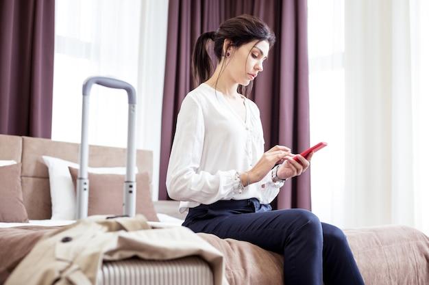 W hotelu. poważna młoda kobieta siedzi na łóżku hotelowym podczas podróży służbowej
