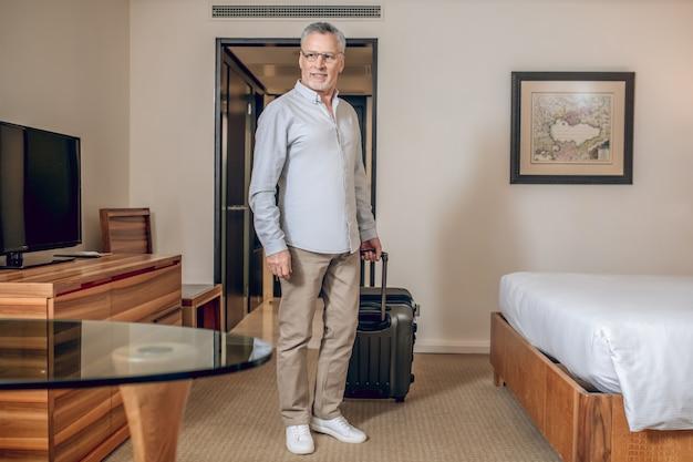 W hotelu. siwowłosy pewny siebie mężczyzna w pokoju hotelowym