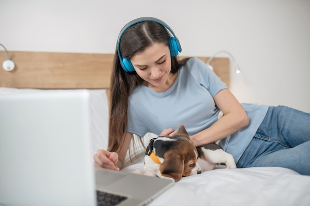 W internecie. ciemnowłosa młoda kobieta słucha muzyki i spędza czas w sieci