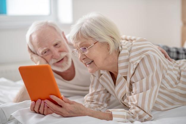 W internecie. siwowłosa kobieta pokazująca mężowi coś na tablecie