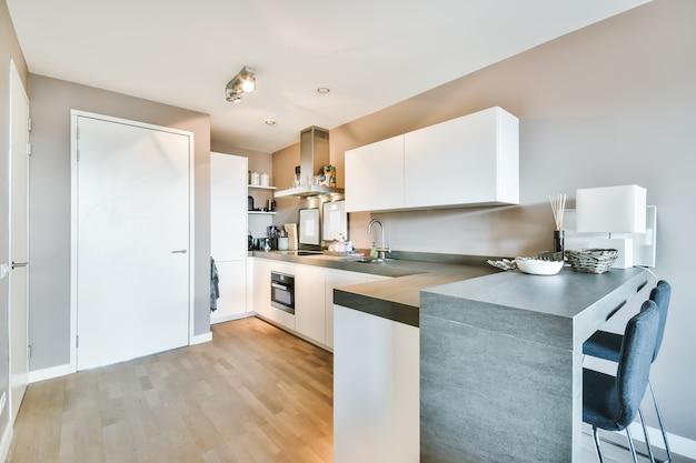 W jasnej kuchni współczesnego mieszkania znajdują się narożne szafki i stół z krzesłami