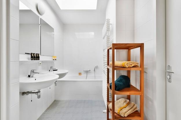 W jasnej łazience nowoczesnego mieszkania znajdują się półki z ręcznikami i suszarka przy umywalkach z lustrami i wanną
