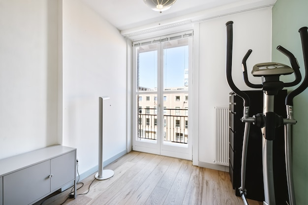 W jasnym pomieszczeniu nowoczesnego mieszkania znajduje się automat schodowy oraz półki przy drzwiach