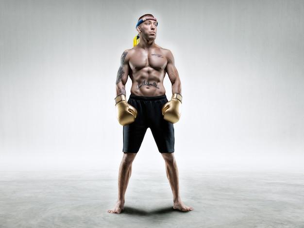 W jasnym pomieszczeniu stoi zawodowy zapaśnik. mieszane sztuki walki, muay thai, koncepcja kickboxingu. różne środki przekazu