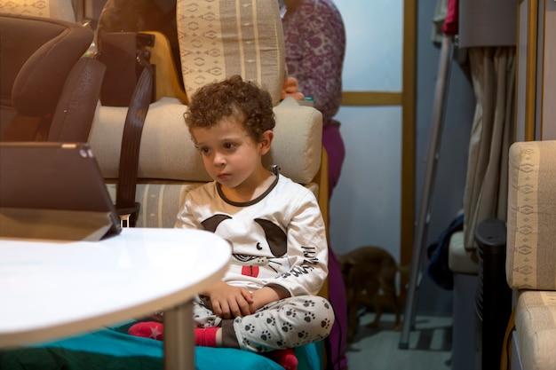 W kamperze dziecko czeka, aż mama ugotuje mu obiad, siedząc na tablecie