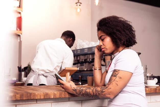 W kawiarni. miła miła kobieta przy użyciu swojego smartfona, czekając na kawę