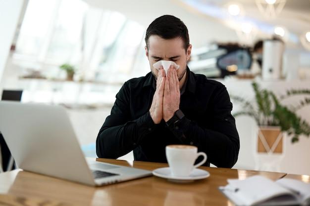 W kawiarni przyszedł do pracy chory z katarem. zmęczony mężczyzna w czarnej koszuli wydmuchuje nos w miejscu publicznym. odizoluj się, jeśli zachorujesz. koncepcja pobytu w domu. filiżanka kawy i laptopa na stole.