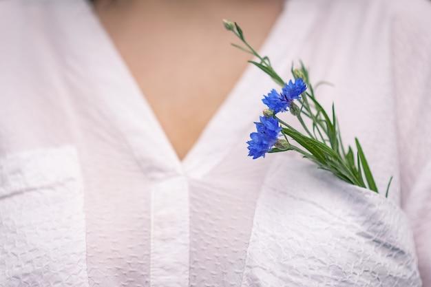 W kieszeni białej bluzki dziewczyny znajdują się dwa niebieskie chabry.