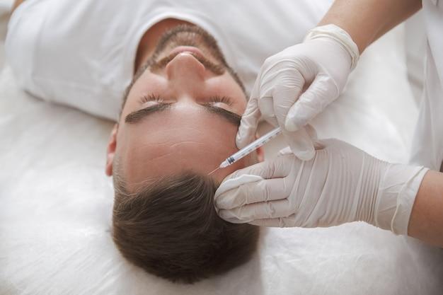 W klinice urody klient płci męskiej otrzymuje leczenie zastrzykami przeciw wypadaniu włosów