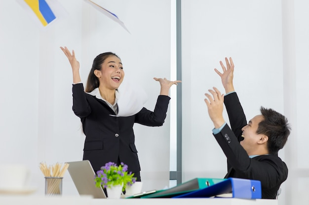 W koncepcji udana i bardzo się cieszę i rzucam papiery o pracy zakończonej i zakończonej. asian para mężczyzna i kobieta biuro ludzie bardzo szczęśliwi, więc oboje rzucają papier.