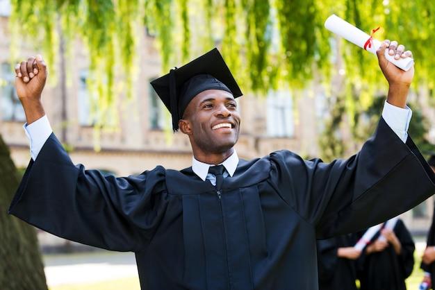 W końcu ukończyłem szkołę! szczęśliwy młody afrykanin w sukniach ukończenia szkoły, trzymający dyplom i unoszący ręce w górę, podczas gdy jego przyjaciele stoją w tle