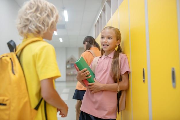 W korytarzu. chłopiec i dziewczynka rozmawiają na korytarzu, stojąc w pobliżu szafek