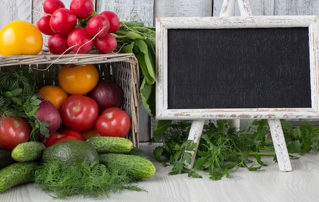 W koszu cebula, pietruszka, koperek, pomidory, rzodkiewki, awokado, ogórki i tablica do pisania z copyspace
