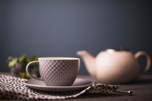 W kratkę deseniowa herbaciana filiżanka na polce kropkował tkaninę na stole