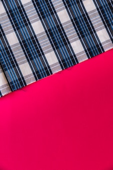 W kratkę deseniowa tkanina na czerwonym tle