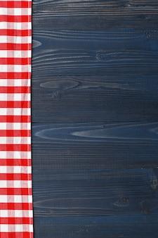 W kratkę obrus na drewnianym stołowym tle