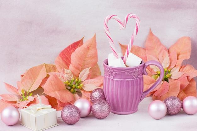 W kubku, piankach, piankach, słodyczach na patyku, różowej poinsecji, kulkach i pudełku