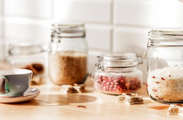 W kuchni są słoiki z ryżem i fasolą. obok puszek na spodeczku filiżanka herbaty i ciasteczka. poziome zdjęcie