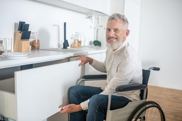W kuchni. siwowłosy niepełnosprawny mężczyzna w kuchni ładnie się uśmiecha