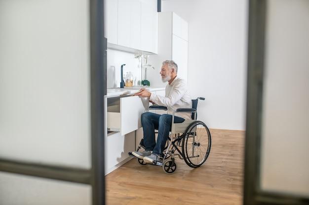 W kuchni. siwowłosy niepełnosprawny mężczyzna w kuchni przygotowujący śniadanie