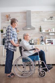 W kuchni stara kobieta patrzy na niepełnosprawnego męża poruszającego się na wózku inwalidzkim. niepełnosprawnych starszy mężczyzna siedzi na wózku inwalidzkim w kuchni patrząc przez okno. mieszkanie z osobą niepełnosprawną. żona pomaga