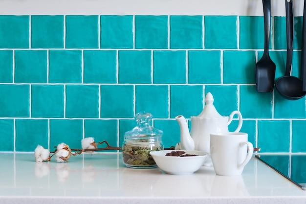 W kuchni znajdują się ciemnoszare, płaskie szafki z przodu połączone z białymi kwarcowymi blatami i błyszczącą niebieską płytką pielęgnacyjną.