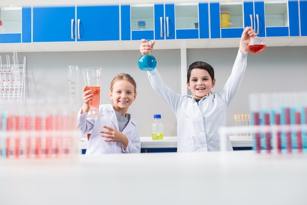 W Laboratorium. Pozytywne Radosne Małe Dzieci, Uśmiechając Się I Patrząc Na Ciebie, Będąc W Laboratorium Chemicznym Premium Zdjęcia