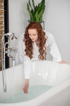 W łazience. ładna ruda kobieta w białym szlafroku przygotowuje się do kąpieli