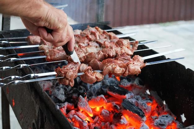 W lecie grill jest gotowany na grillu. mięso na szaszłykach. dym z węgli.