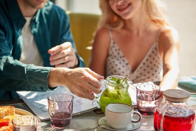 W lekkiej kawiarni mężczyzna wlewa słodki napój do szklanek dla kobiety