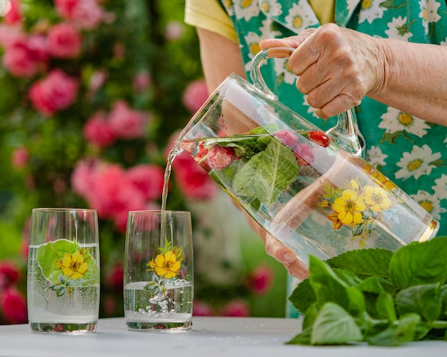 W letnim ogrodzie wiejskiego domu. miłego letniego weekendu, zrelaksuj się. napój bezalkoholowy (lemoniada) z miętą i liśćmi mięty, zdrowy produkt