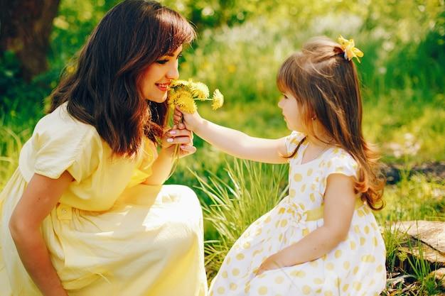 W letnim parku w pobliżu zielonych drzew, mama chodzi w żółtej sukience i jej ślicznotka