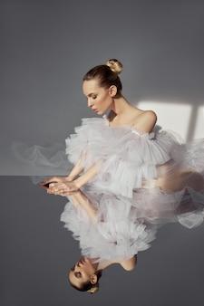 W lustrze odbija się portret romantycznej kobiety piękna w lekkiej sukience.