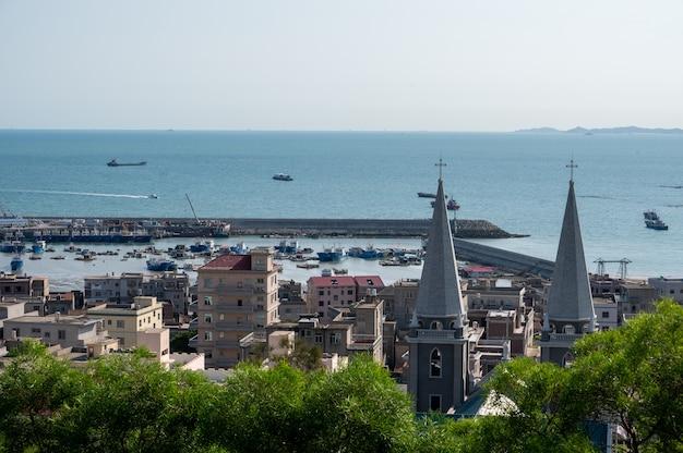 W małym miasteczku nad morzem znajduje się kościół. krzyż na szczycie kościoła bardzo rzuca się w oczy