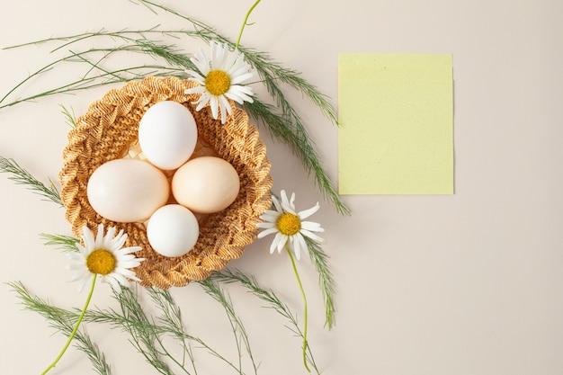 W małym wiklinowym koszu. leżą cztery jaja kurze i kwiaty rumianku. obok arkusza z napisem. widok z góry. układ.