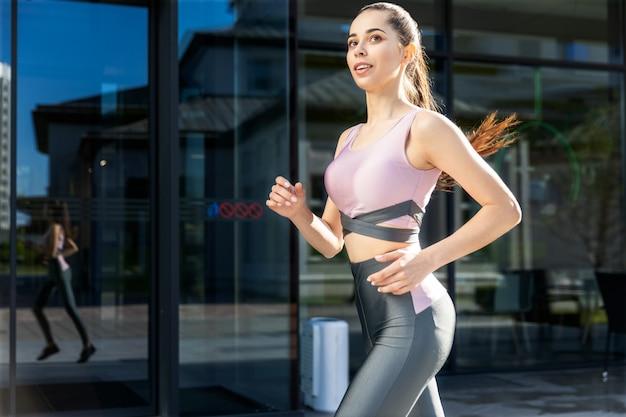 W mieście biegnie młoda piękna kobieta z kucykiem w sportowym stroju