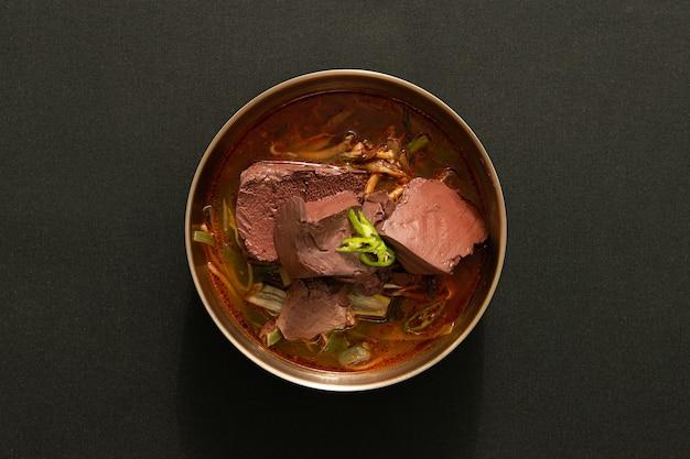 W misce jest zupa mięsna tło ma czarną teksturę