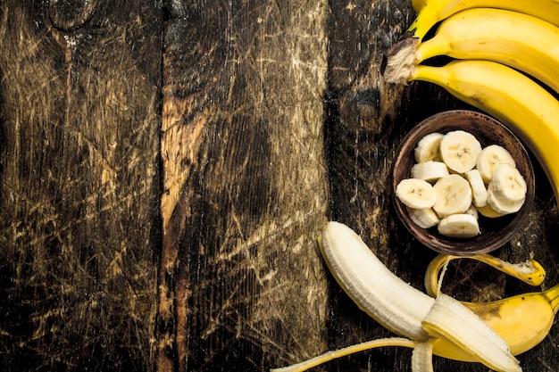 W misce pokrojony dojrzały banan. na drewnianym stole.
