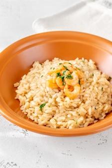 W misce porcja risotto przyozdobiona krewetką