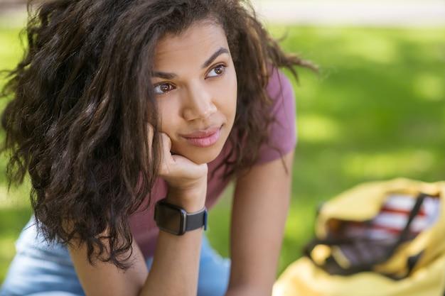 W myślach. długowłosa śliczna mulatka siedząca na ławce z zamyślonym spojrzeniem